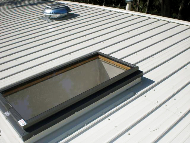 light grey metal roof with custom skylight and solar powered attic vent