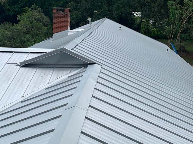 Silver metal roof with brick chimney